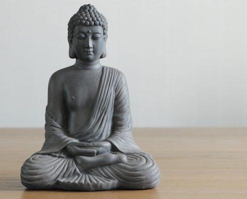 Graue Buddhafigur auf Holz mit weißem Hintergrund