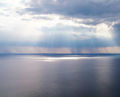 Meer und Wolkenhimmel mit Sonnenstrahlen