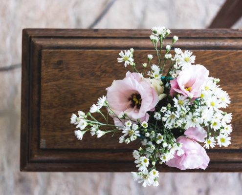 Holzsarg für Erdbestattung mit Blumenarrangement