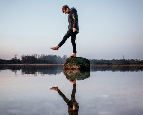 Mann balanciert auf Stein im Wasser